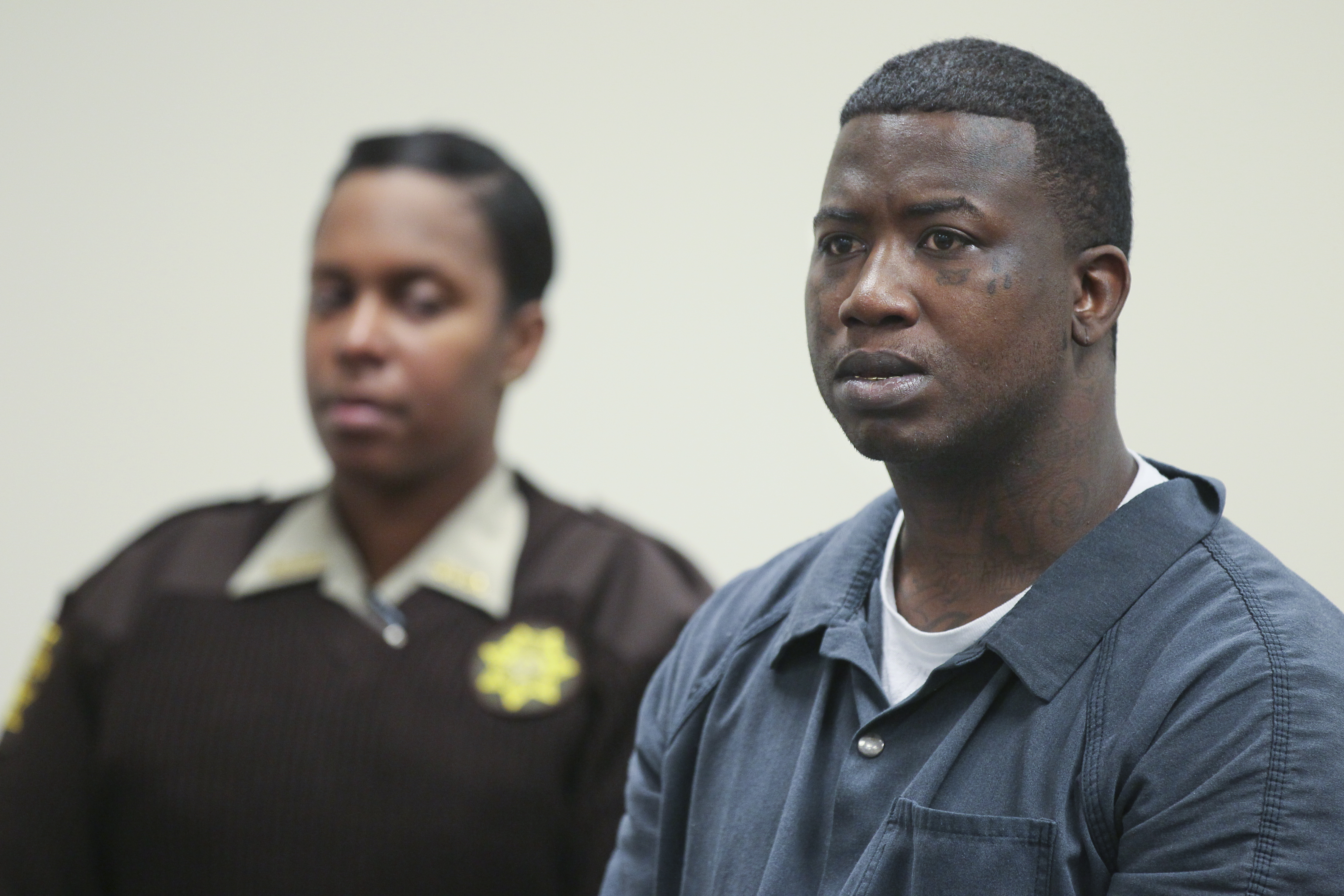 "Mar. 27, 2013 Atlanta: Fulton County Sheriff deputy T. Reynolds (left) looks on as defendant Radric Davis (right) listens. Rapper Gucci Mane was denied bond Wednesday at his first court appearance after his arrest for allegedly assaulting a soldier earlier this month at an Atlanta nightclub. His next court date is April 10. The musician, whose real name is Radric Davis, was booked into the Fulton County Jail Tuesday, charged with aggravated assault with a weapon, according to online jail records. Fulton County sheriff's spokeswoman Tracy Flanagan said Davis turned himself in at the jail about 11:30 p.m. Tuesday, and will face a magistrate for a first appearance at 11 a.m. Wednesday. Channel 2 Action News reported last week that Atlanta police had issued a warrant for the rapper following the March 16 incident at the Harlem Nights club on Courtland Street. The alleged victim told Channel 2 that Davis hit him in the head with a champagne bottle after he asked to take a photo with the rapper. ""I'm in the military. I wanted to get a picture with Gucci Mane, is it okay?"" the soldier said he asked a security guard. ""I was speaking to the security guard, and Gucci Mane hit me in the head with a bottle,"" the solder told Channel 2. The soldier told the station that he went to Grady Memorial Hospital by ambulance, and his injury required 10 stitches. JOHN SPINK / JSPINK@AJC.COM"